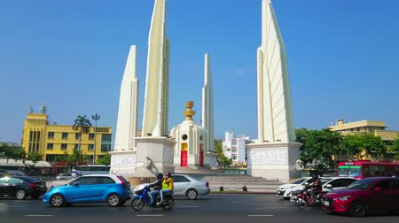 sudeste : BANGKOK, THAILAND - APRIL 24, 2019: The circle traffic in Ratchadamnoen Avenue with a view on Democracy Monument, surrounded by four wing-like structures, on April 24 in Bangkok