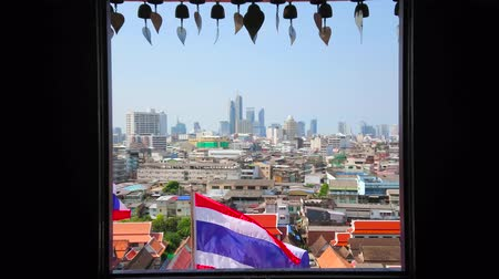 nakhon : Bangkok skyline with waving National Thai flag and Buddhist prayer bells, hanging over the window of Wat Saket Temple, located atop the Golden Mount, Thailand