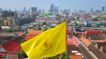 kolumny : BANGKOK, THAILAND - APRIL 24, 2019: The waving yellow Royal flag on top of Golden Mount with a view on red gable roofs of Wat Saket temples and modern skyscrapers on horizon, on April 24 in Bangkok