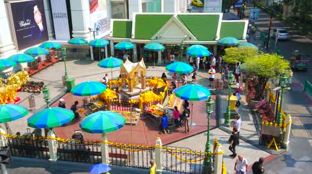 parasol : BANGKOK, THAILAND - APRIL 24, 2019: The small golden Erawan Shrine is popular landmark of New Town, surrounded by busy streets, high-rises, business centers and shopping malls, on April 24 in Bangkok