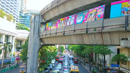 pathum wan : BANGKOK, THAILAND - APRIL 24, 2019: The busy traffic in Ratchaprasong junction, cars stand at traffic light under the railway bridge with riding skytrain, on April 24 in Bangkok