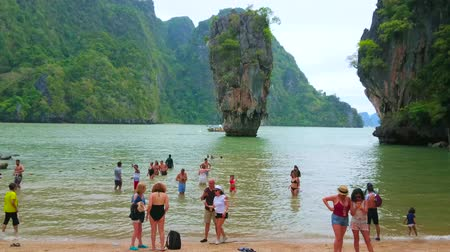 haven : AO PHANG NGA, THAILAND - APRIL 28, 2019: The crowded beach of James Bond Island (Khao Phing Kan) with a view on Raya Ring island rocks and karst tower of Ko Ta Pu, on April 28 in Ao Phang Nga Stock Footage