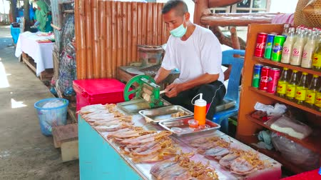 drijvende markt : KO PANYI, THAILAND - APRIL 28, 2019: The market vendor prepares snacks of dry squids, using hand press in a stall of floating village market, on April 28 in Ko Panyi