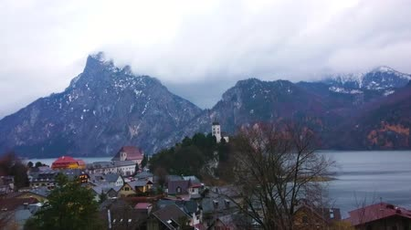 エディフィス : The thunderstorm evening in Traunkirchen with a view on Traunstein mount in rainy clouds, dark waters of Traunsee lake and white slender Johannesbergkapelle, Salzkammergut, Austria.