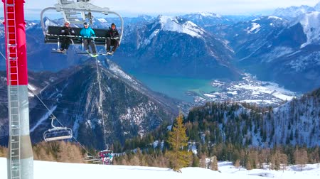 hegytömb : EBENSEE, AUSTRIA - FEBRUARY 24, 2019: The chairlift, carrying sportsmen to the top of Feuerkogel mount with a view on Traunsee lake valley amid rocky snowy Dachstein Alps, on february 24 in Ebensee Stock mozgókép