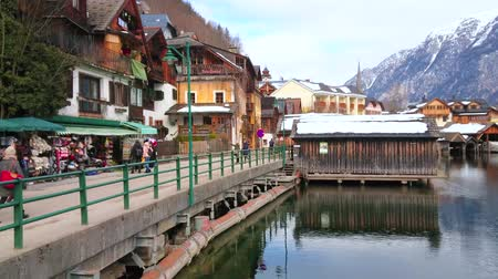 hallstatter see : HALLSTATT, AUSTRIA - FEBRUARY 21, 2019: Embankment of Hallstattersee boasts extant historical houses, small tourist market with souvenirs, authentic bars and cafes, on February 21 in Hallstatt Stock Footage