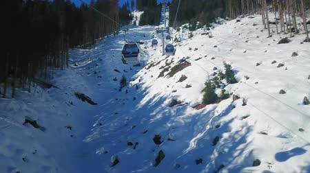 ski run : ZELL AM SEE, AUSTRIA - FEBRUARY 28, 2019: The fast gondolas of modern Trassxpress cableway ride along the steep snowy slope of Schmittenhohe mount, on February 28 in Zell Am See