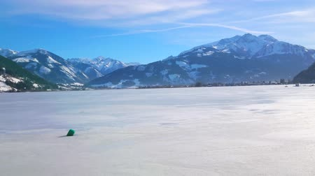 elisabeth : The sun shines on ice of frozen Zeller See lake, surrounded by snowy Alps, Zell am See, Austria
