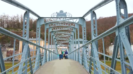 mozart : SALZBURG, AUSTRIA - MARCH 1, 2019: People walk through the metal construction of Mozartsteg footbridge over the Salzach river, on March 1 in Salzburg
