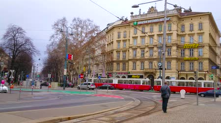 viennese : VIENNA, AUSTRIA - MARCH 2, 2019: The Classical Viennese architecure and tall trees stretches along the Karntner Ring boulevard with riding cars and vintage trams, on March 2 in Vienna