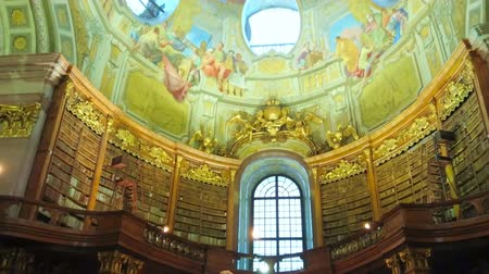 hofburg : VIENNA, AUSTRIA - MARCH 2, 2019: The The great interior of Prunksaal of National Library with vintage bookcases, books, marble statue of Emperor Charles VI and stunning dome, on March 2 in Vienna
