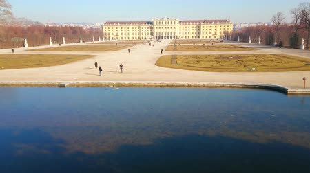 schonbrunn : VIENNA, AUSTRIA - FEBRUARY 19, 2019: The view on Schonbrunn palace and  garden (Shlosspark, Bundesgarten) with clear surface of Neptune fountains pond on the foreground, on February 19 in Vienna