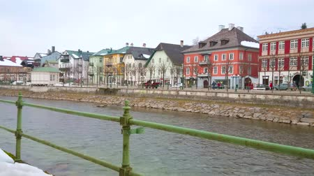 townhouse : BAD ISCHL, AUSTRIA - FEBRUARY 25, 2019: The riverside cityscape of the famous spa resort with preserved historical edifices and horse-drawn carriage, riding along the bank, on February 25 in Bad Ischl