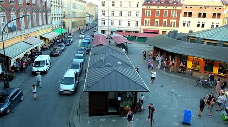 クラクフ : KRAKOW, POLAND - JUNE 20, 2018: The line of tourist cafes, located in historical townhouses in New Square (Plac Nowy) of Kazimierz Jewish Quarter, on June 20 in Krakow.