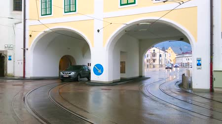 tramwaj : GMUNDEN, AUSTRIA - FEBRUARY 22, 2019: The urban scene with traffic through the arch of K-Hof (Kammerhofmuseen) building to the Traunbrucke bridge, on February 22 in Gmunden.