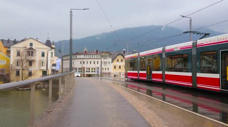 tükrözött : GMUNDEN, AUSTRIA - FEBRUARY 22, 2019: The red tram, driving along the wet Traun bridge (Traunbrucke), is reflected in puddles on the dark road, on February 22 in Gmunden