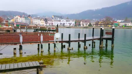 gaivota : Walk along embankment of Traun lake (Traunsee) with a view on old pier and foggy old town on the background, on February 22 in Gmunden