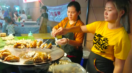 bazar : CHIANG MAI, THAILAND - MAY 4, 2019: Young vendors fry gyoza (jiaozi, potstickers) dumplings with meat, shrimps and vegetables in Saturday Night Market, Wualai walking street, on May 4 in Chiang Mai