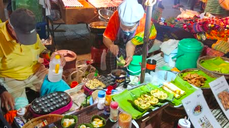 bazar : CHIANG MAI, THAILAND - MAY 4, 2019: The couple of senior vendors cooks and sells fried quail eggs in stall of Saturday Night Market in Wualai walking street, on May 4 in Chiang Mai