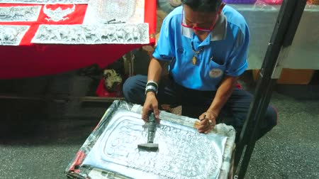 網目模様 : CHIANG MAI, THAILAND - MAY 4, 2019: The silversmith creates ornate Buddha footprint on plate in open air silver workshop, Saturday Night Market in Wualai walking street, on May 4 in Chiang Mai 動画素材