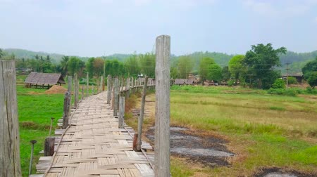 poo : Enjoy panorama of old Su Tong Pae Bamboo Bridge - long narrow and curved construction with tall wooden poles, stretching along the agricultural lands and paddy fields in Mae Hong Son suburb, Thailand
