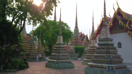 reclináveis : BANGKOK, THAILAND - APRIL 22, 2019: The pleasant evening walk among the ornate chedies of Wat Pho temple, enjoying magnificent architecture of famous religion complex, on April 22 in Bangkok