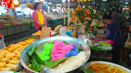 manga : CHIANG MAI, THAILAND - MAY 4, 2019: The stall of farmers Gate Market sells ingredients for mango sticky rice Thai dessert - colored rice, fresh mangos and coconut milk, on May 4 in Chiang Mai Stock Footage