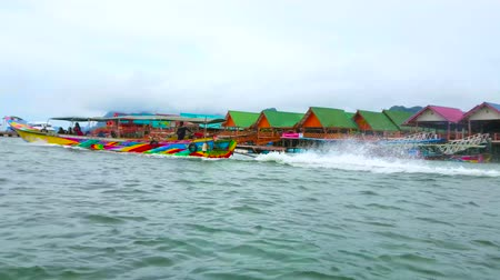каноэ : KO PANYI, THAILAND - APRIL 28, 2019: The   speedboat trip along the shore of Ko Panyi (Koh Panyee) floating Muslim village with colored wooden stilt huts, on April 28 in Ko Panyi Стоковые видеозаписи