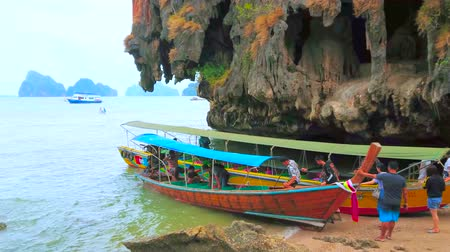 石灰岩 : AO PHANG NGA, THAILAND - APRIL 28, 2019: TThe longtail boats wait the tourists in the tiny haven of James Bond Island (Khao Phing Kan), on April 28 in Ao Phang Nga