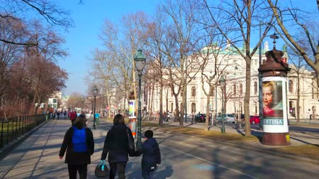 streetlights : VIENNA, AUSTRIA - FEBRUARY 17, 2019: Walk the shady alley along Burgring avenue with a view on Burgtheater (theatre) behind the trees, on February 17 in Vienna.