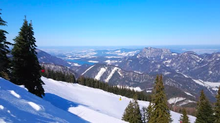 ski run : The winter scenery with tall spruce trees, white slope of Zwolferhorn, gondolas of cable car and Alpine landscape of Salzkammergut, St Gilden, Austria Stock Footage
