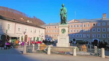 michael : SALZBURG, AUSTRIA - FEBRUARY 27, 2019: The architectural ensemble of Mozart square (Mozarplatz) with monument amid historical buildings and cafes, on February 27 in Salzburg.