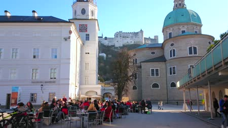 столовая гора : SALZBURG, AUSTRIA - FEBRUARY 27, 2019: Residenzplatz square with a view on Residence Palace, apse of the Cathedral, tables of outdoor restaurants and Castle atop the hill, on February 27 in Salzburg