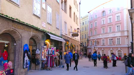 townhouse : SALZBURG, AUSTRIA - FEBRUARY 27, 2019: The narrow shopping street of Altstadt (old town) with many small stores, offering sport stuff, clothes, souvenirs and local foods, on February 27 in Salzburg