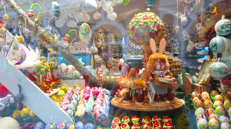 statuette : SALZBURG, AUSTRIA - FEBRUARY 27, 2019: The showcase of the handicraft store with traditional Easter toys, painted eggs, wooden Easter Bunnies and spinning music box, on February 27 in Salzburg Stock Footage