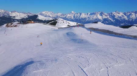 snowboarden : Panorama of long slopes of the Schmitten mountain with comfortable pistes, that attract the skiers and boarders to visit Zell am See Alps resort, Austria. Stockvideo