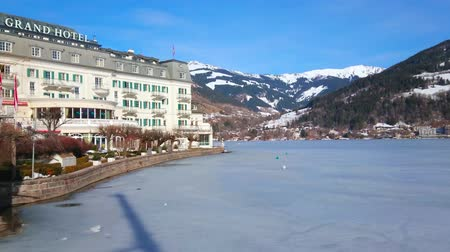 산책 길 : ZELL AM SEE, AUSTRIA - FEBRUARY 28, 2019: The luxury Grand Hotel, located on the bank of frozen Zeller See lake with scenic mountain range on background, on February 28 in Zell Am See