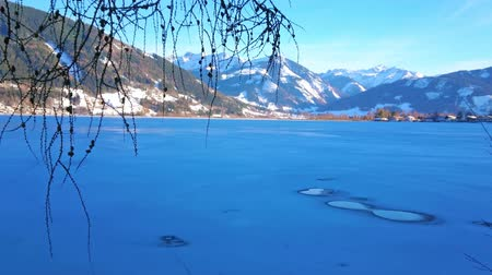 elisabeth : The scenic blue frozen surface of Zeller see lake with small ice holes and snowy Alps on background, Zell am See, Austria