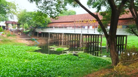 言うこと : LAMPHUN, THAILAND - MAY 8, 2019: The shady park on the bank of Kuang river, covered with green plants, with a view on old Tha Sing bridge on stilts, that houses souvenir market, on May 8 in Lamphun