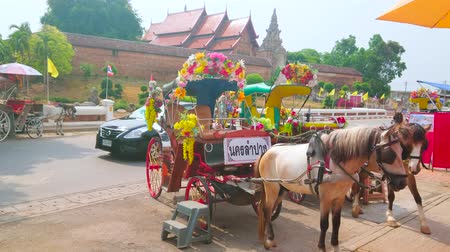 cavalo vapor : LAMPANG, THAILAND - MAY 8, 2019: The horse-drawn carriage attracts tourists to make a trip, starting in front of medieval Wat Phra That Lampang Luang Temple, on May 8 in Lampang Stock Footage