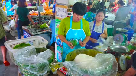 banan : LAMPANG, THAILAND - MAY 8, 2019: The food sellers in busy Ratsada market offers ready-made rice, wrapped in banana leaf, on May 8 in Lampang