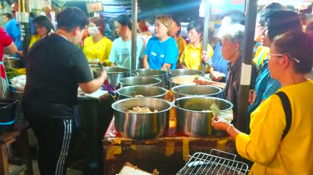 összeg : LAMPANG, THAILAND - MAY 8, 2019: Chaotic queue of people in front of the counter of food stall, offering large amount of take away dishes of Thai cuisine in Ratsada market, on May 8 in Lampang