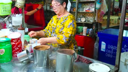 sweetened : LAMPANG, THAILAND - MAY 8, 2019: The vendor of tiny stall in Ratsada market  prepares traditional Thai ice coffee with sweetened condensed milk, using flannel drip, on May 8 in Lampang