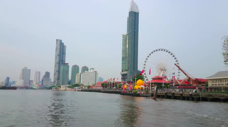 luna park : BANGKOK, THAILAND - MAY 15, 2019: Enjoy the trip along Chao Phraya river with a view on Asiatique The Riverfront shopping mall, its ferris wheel and skyscrapers on background, on May 15 in Bangkok