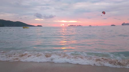geçen : Blue hour is the best time to relax on Patong beach, observe the last rays of sunset, rippled surface of Andaman sea, gentle tide and speedboat with flying parasail, Patong, Phuket, Thailand