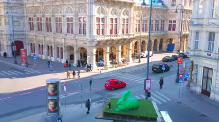 crowded : VIENNA, AUSTRIA - FEBRUARY 17, 2019: The busy Albertinaplatz with a view on corner of State Opera and green plastic installation of Durer Hare, located on the roof of kiosk, on February 17 in Vienn Stock Footage