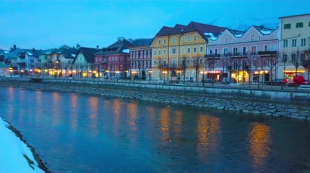 crepúsculo : BAD ISCHL, AUSTRIA - FEBRUARY 20, 2019: Watch the winter old town on blue hour, its historical houses, stretching along embankment, are reflected in waters of Traun river, on February 20 in Bad Ischl Stock Footage