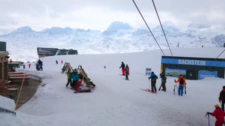 hegytömb : OBERTRAUN, AUSTRIA - FEBRUARY 21, 2019: Skiers at the top station of Dachstein Krippenstein cable car, here people can rent equipment, visit cafe or prepare for downhill, on February 21 in Obertraun. Stock mozgókép
