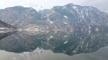 falu : Walk by Hallstattersee lake and observe snowy Dachstein mountain range, reflecting in clear lake waters, Hallstatt, Salzkammergut, Austria.
