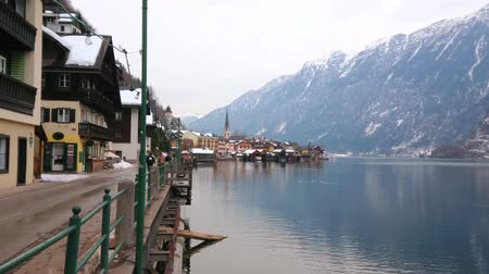 mercado : HALLSTATT, AUSTRIA - FEBRUARY 21, 2019: Walk Seestrasse embankment and enjoy old town with its landmarks, Halstattersee lake and snowy Alpine slopes, on February 21 in Hallstatt